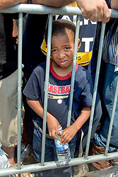 2nd Sept, 2005. New Orleans, Louisiana.<br /> A young boy trapped against railings in the baking sun awaiting evacuation from the hellish Superdome in New Orleans..<br /> Photo Credit; Charlie Varley/varleypix.com