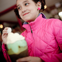 A girl in a pink coat eats a root beer float at the Skyline diner in Portland, Oregon