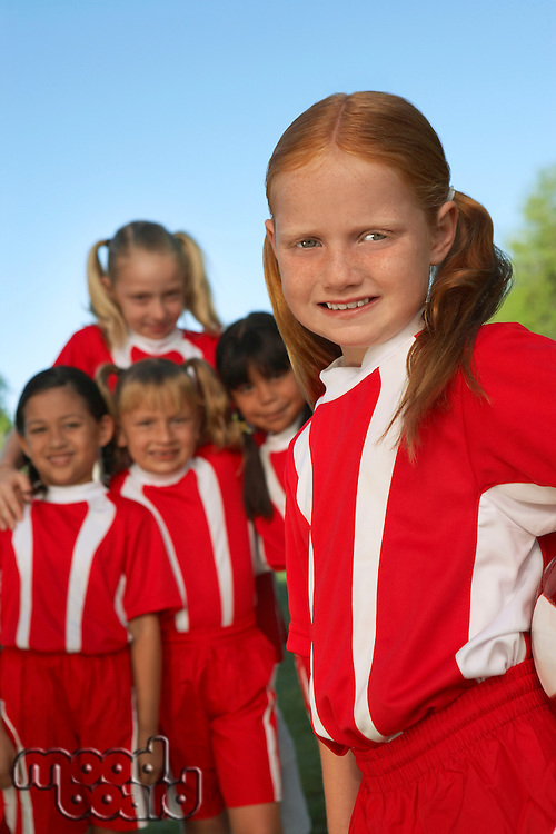 Group of girl soccer players (7-9 years) standing on field, portrait