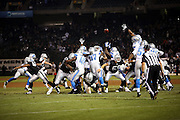 Detroit Lions players leap and try to block the extra point in vain as Oakland Raiders kicker Sebastian Janikowski (11) kicks the game winning PAT with six seconds left in the 4th quarter during the 2014 NFL preseason football game against the Detroit Lions on Friday, Aug. 15, 2014 in Oakland, Calif. The Raiders won the game 27-26. ©Paul Anthony Spinelli