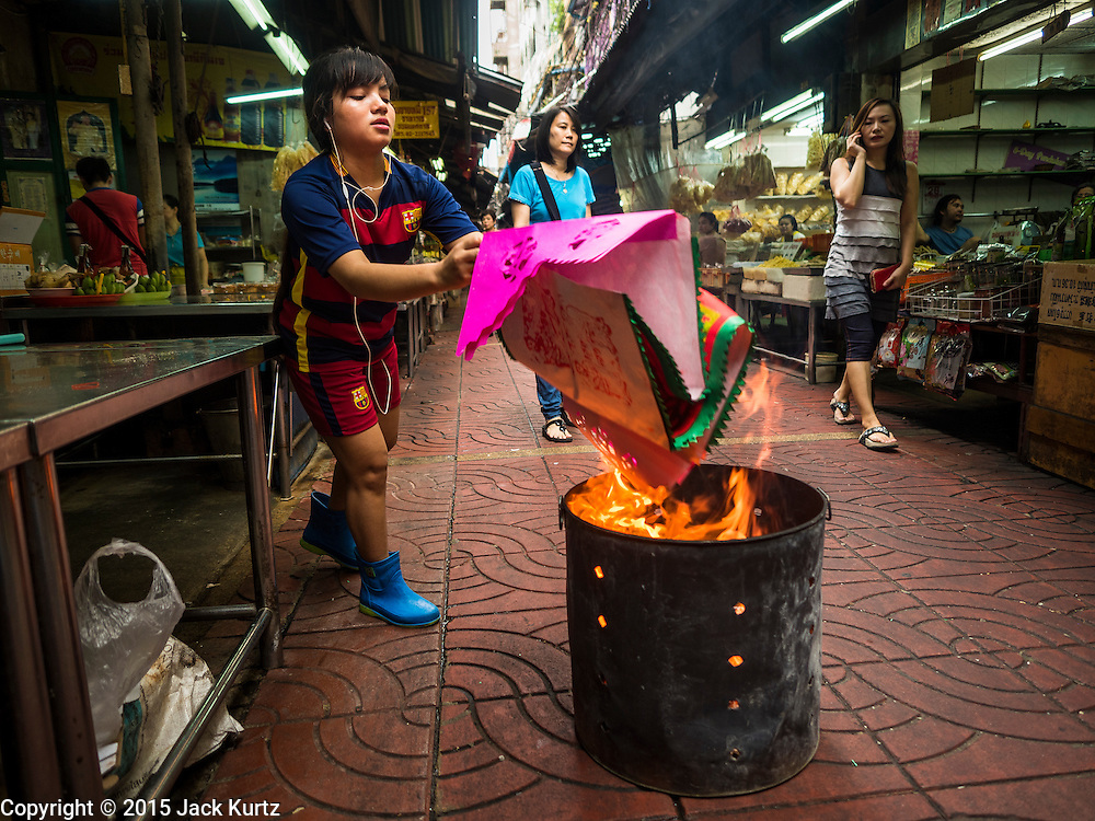 28 AUGUST 2015 - BANGKOK, THAILAND: A woman burns paper clothes for her  ancestors, now ghosts, on Hungry Ghost Day in Bangkok's Chinatown. Mahayana  Buddhists believe that the gates of hell are opened on the full moon of the seventh lunar month of the Chinese calendar, and the spirits of hungry ghosts allowed to roam the earth. These ghosts need food and merit to find their way back to their own. People help by offering food, paper money, candles and flowers, making merit of their own in the process. Hungry Ghost Day is observed in communities with a large ethnic Chinese population, like Bangkok's Chinatown.       PHOTO BY JACK KURTZ