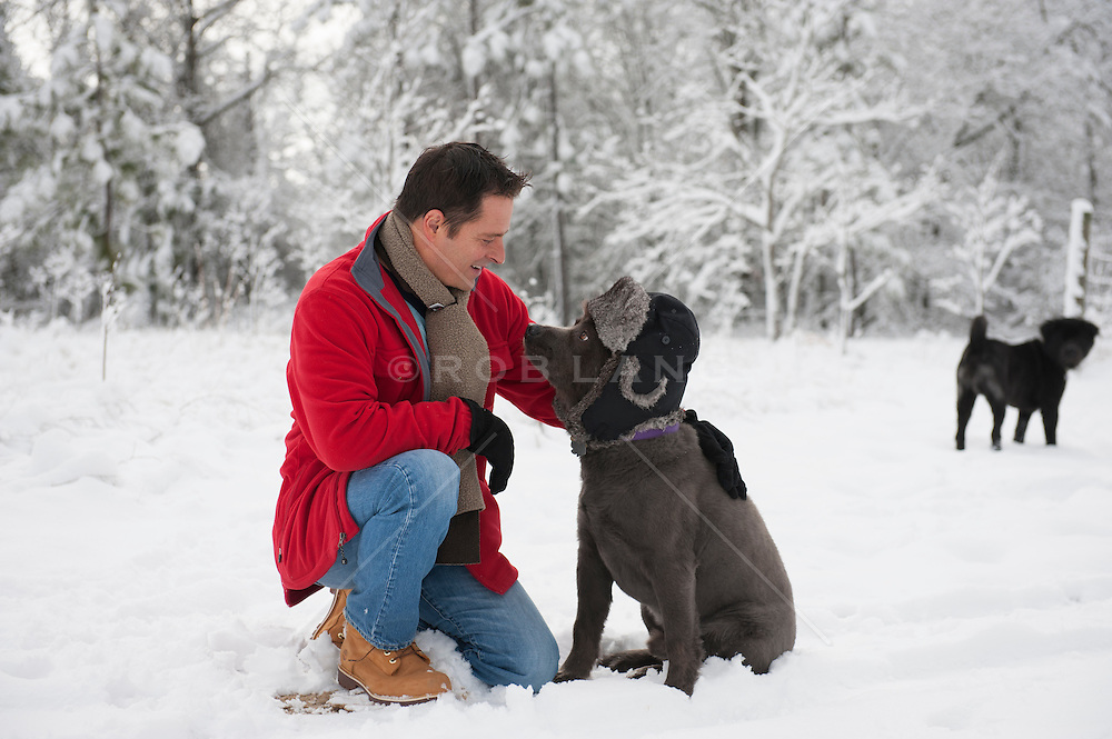 man with his dog wearing a hat in the snow