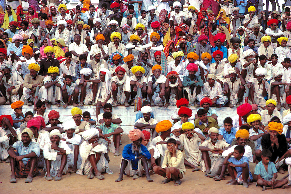 Spectators at Pushkar Fair, in Rajasthan, India, sit patiently in their striking red, orange and yellow turbans.