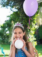 Portrait of young girl (10-12) wearing tiara blowing up balloons