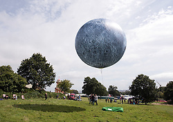 © Licensed to London News Pictures. 11/08/2016. Bristol, UK. Bristol International Balloon Fiesta 2016. Picture of 'The Museum of the Moon' by international artist Luke Jerram. A 7m in diameter sphere, printed with NASA imagery of the Moon, made by Cameron Balloons in Bristol and filled with helium, the 'moon' will float above Ashton Court during the Bristol International Balloon Fiesta and light up at night. The Bristol International Balloon Fiesta is Europe's largest ballooning event and takes place from Thursday 11th August – Sunday 14th August, attracting half a million people over four days. This year 150 hot air balloons will attend, taking off in mass ascents at dawn and dusk. On Thursday and Saturday evenings, 30 balloons will tether in the main arena and light up in sequence to music for the famous Night Glows. Photo credit : Simon Chapman/LNP
