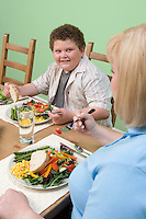 Overweight mother with overweight son having healthy meal