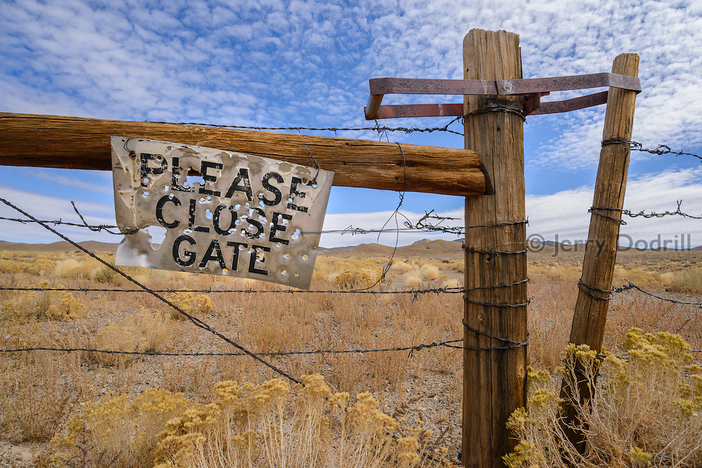 "Along a rural stretch of State Highway 376 near Tonopah, Nevada, a bullet-ridden sign attached to a barbed wire fence reads ""PLEASE CLOSE GATE""."