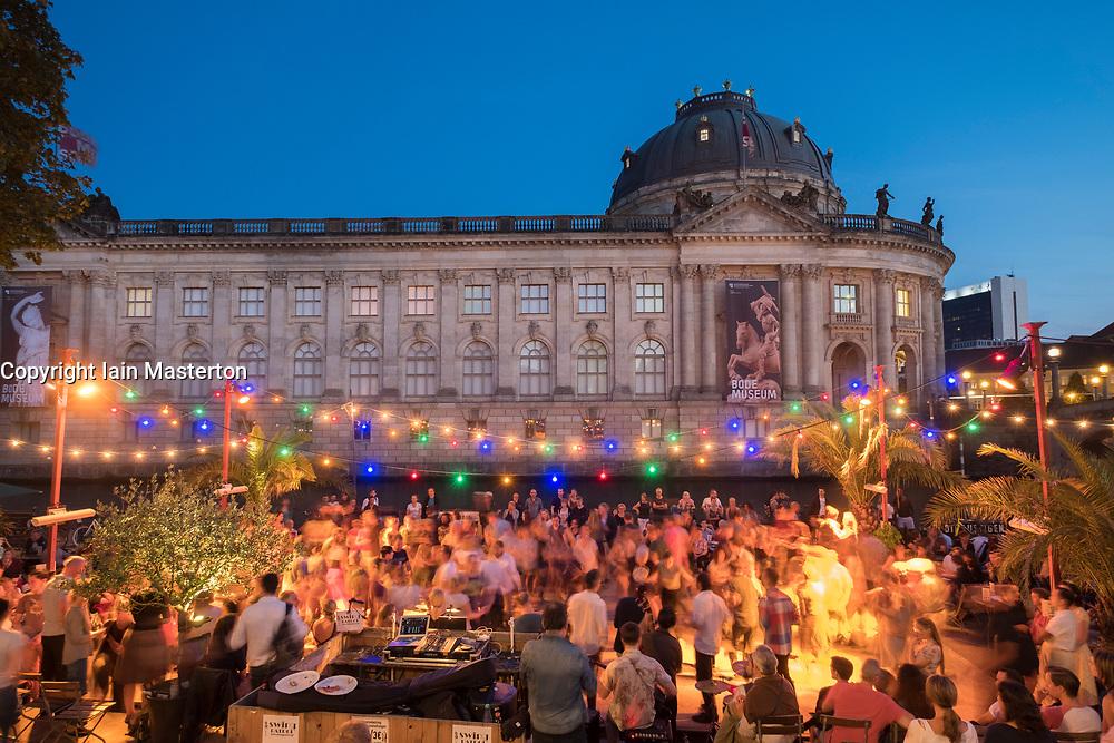 Outdoor dancing on summer evening at riverside bar in Monbijou Park in Berlin Germany