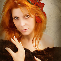 woman with red roses in her hair, looking at camera