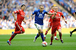 John Heitinga of Everton (centre) with Jay Spearing (right) and Luis Suarez of Liverpool during the Budweiser FA Cup semi final match between Liverpool and Everton at Wembley on Saturday 14 April 2012 (Photo by Rob Munro)