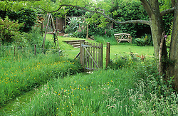 Looking into the garden from the wild, meadow area. Shows wire fence and gate for rabbit protection