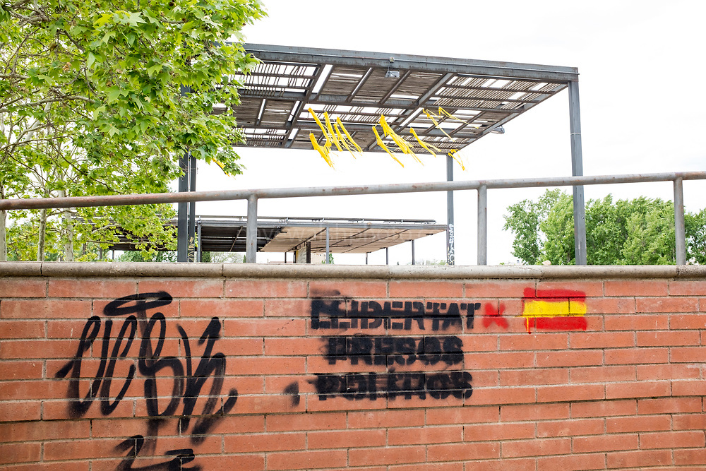 Sant Cugat del Valles, just outside Barcelona. Graffiti supporting Catalan political prisoners scratched out and replaced by the Spanish flag. In the background, yellow ribbons supporting the prisoners blow in the wind.