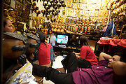 Chatuchak Sunday Market. Watching TV in a folk art store.