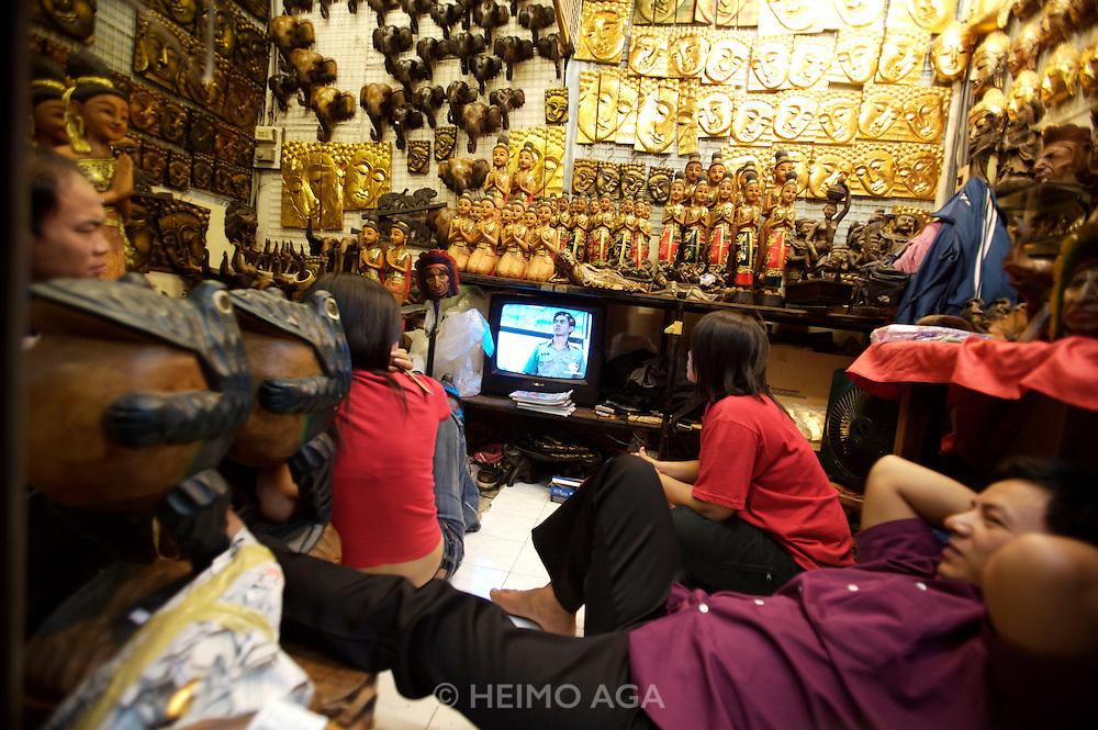Chatuchak Sunday Market. Watching TV in a folk art store.