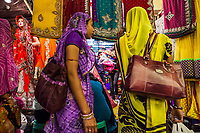 One woman looks at the camera in a Women walk by the many sari shops in a cramped busy sari market in Jaipur, Rajasthan, India.