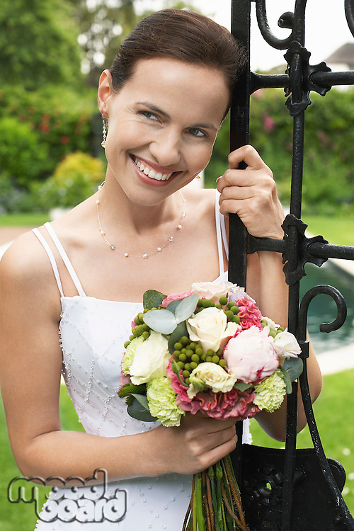 Mid adult bride leaning on gate holding bouquet looking away portrait