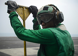 U.S. Navy Airman Christopher Francis, from Atlanta, holds a push-back bar as he waits to conduct flight operations aboard the aircraft carrier USS Nimitz (CVN 68), Aug. 22, 2017, in the Arabian Gulf. Nimitz is deployed in the U.S. 5th Fleet area of operations in support of Operation Inherent Resolve. While in this region, the ship and strike group are conducting maritime security operations to reassure allies and partners, preserve freedom of navigation, and maintain the free flow of commerce. (U.S. Navy photo by Mass Communication Specialist 2nd Class Holly L. Herline)  Please note: Fees charged by the agency are for the agency's services only, and do not, nor are they intended to, convey to the user any ownership of Copyright or License in the material. The agency does not claim any ownership including but not limited to Copyright or License in the attached material. By publishing this material you expressly agree to indemnify and to hold the agency and its directors, shareholders and employees harmless from any loss, claims, damages, demands, expenses (including legal fees), or any causes of action or allegation against the agency arising out of or connected in any way with publication of the material.
