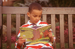 Boy sitting on park bench reading story book,