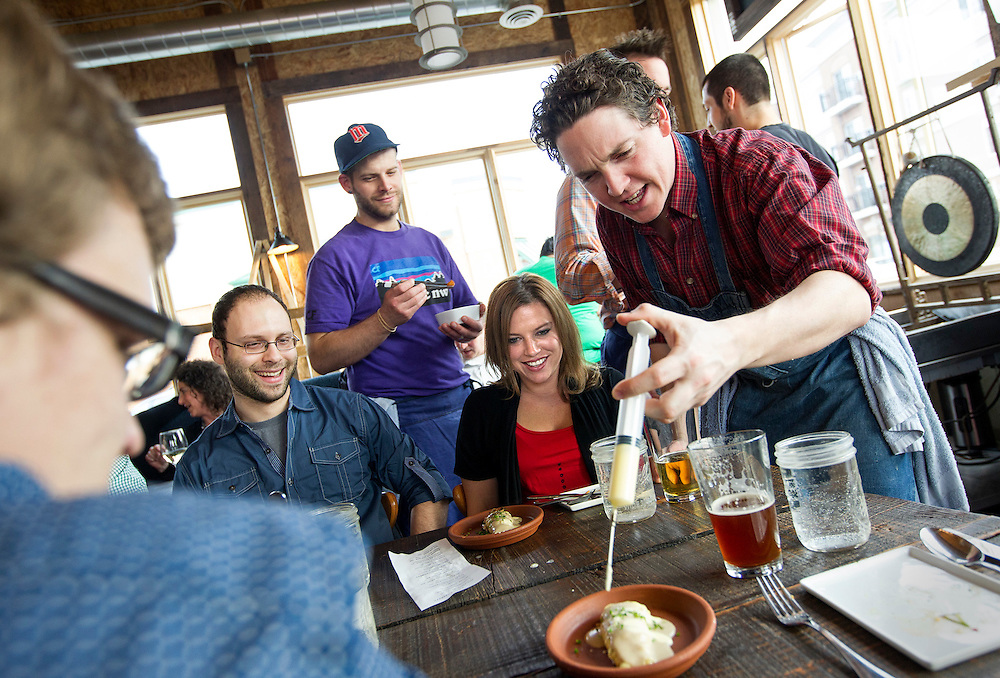 Chef Bob Wood uses a kitchen syringe to inject a saffron-lemon emulsion into a braid of angel hair pasta, one of six touches added tableside during the pasta course. Wood's colleague Tyler Wilcox (center, purple shirt) prepares to contribute another garnish at Travail in Robbinsdale April 18, 2014.