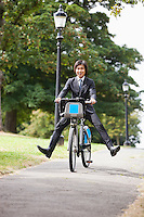 Portrait of young businessman riding bicycle with legs kicked out