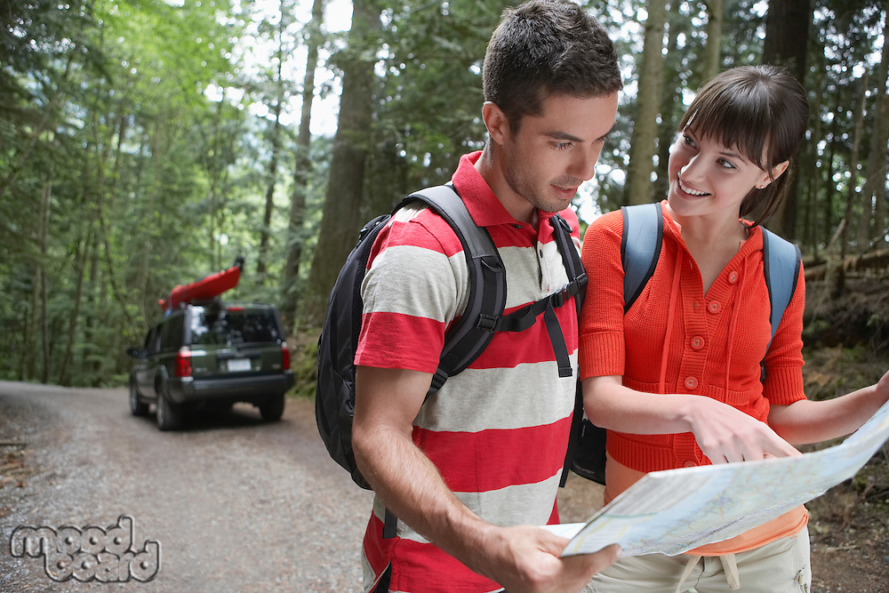 Couple observing map in forest