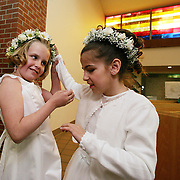 first communion - des moines, may 1 -- Annabelle Costanzo, right, feels the head band worn by best friend Olivia Kennedy before their first communion at Holy Trinity Church Sunday.  Costanzo, who has been blind since birth, will make a trip to Detroit in August to she specialist Michael Trese.  The family is hoping that a new techinique, using an endoscope will reveal more information about her retina, and eventually lead to a possible cornea transplant.  photo by david peterson