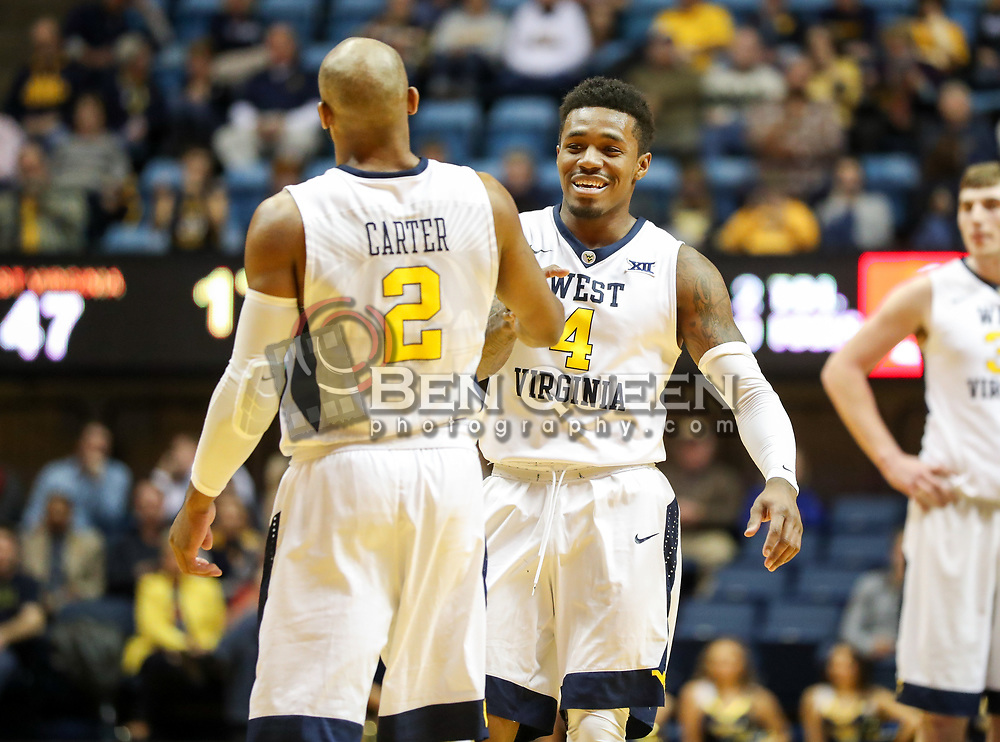Dec 20, 2017; Morgantown, WV, USA; West Virginia Mountaineers guard Daxter Miles Jr. (4) celebrates with West Virginia Mountaineers guard Jevon Carter (2) after scoring his 1000th point during the second half against the Coppin State Eagles at WVU Coliseum. Mandatory Credit: Ben Queen-USA TODAY Sports