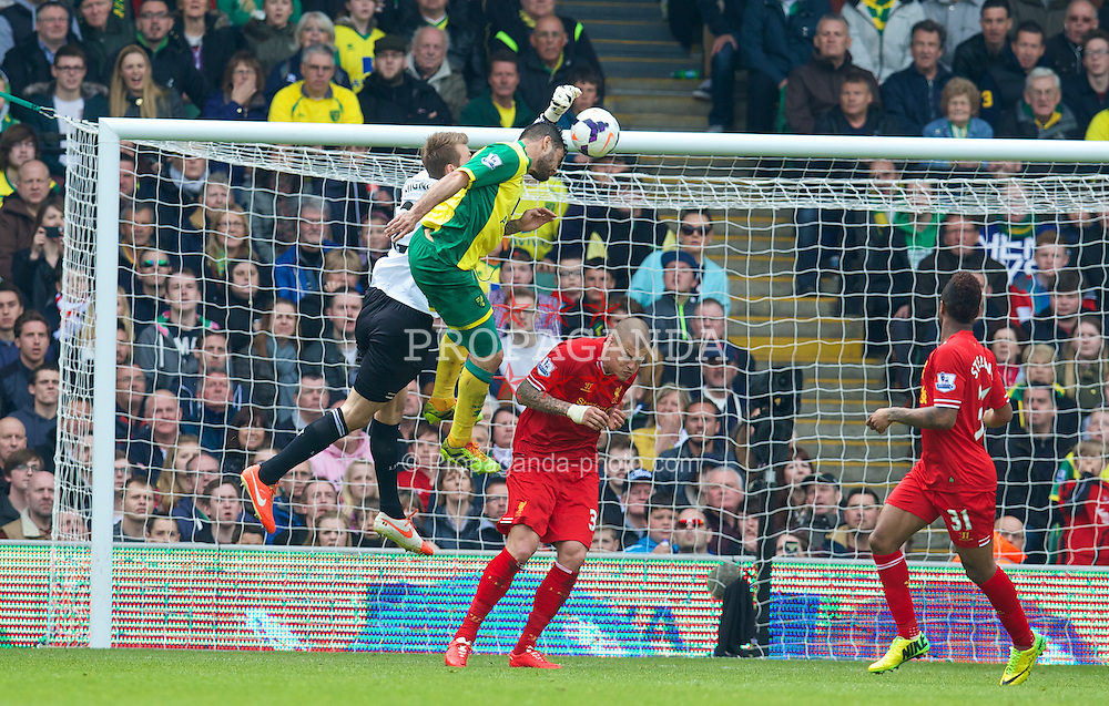 NORWICH, ENGLAND - Sunday, April 20, 2014: Liverpool's goalkeeper Simon Mignolet loses out to Norwich City's Bradley Johnson in the build up to the Canaries' first goal during the Premiership match at Carrow Road. (Pic by David Rawcliffe/Propaganda)