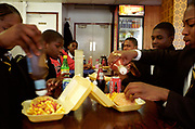 Group of teenagers in school uniform putting ketchup and sauce on take-away burgers and chips Lambeth Walk South London c.2000