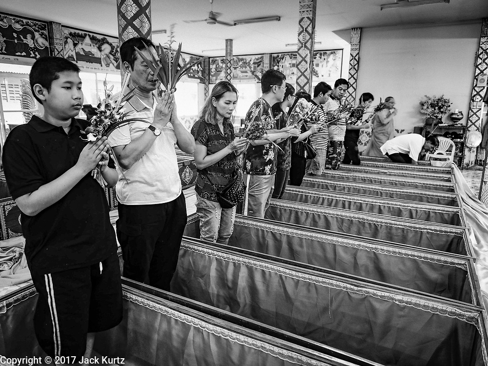 "29 MARCH 2017 - BANG KRUAI, NONTHABURI, THAILAND: People about to go through their ritualistic death during a ""Resurrection Ceremony"" stand in their coffins at Wat Ta Kien (also spelled Wat Tahkian), a Buddhist temple in the suburbs of Bangkok. People go to the temple to participate in a ""Resurrection Ceremony."" Groups of people meet and pray with the temple's Buddhist monks. Then they lie in coffins, the monks pull a pink sheet over them, symbolizing their ritualistic death. The sheet is then pulled back, and people sit up in the coffin, symbolizing their ritualist rebirth. The ceremony is supposed to expunge bad karma and bad luck from a person's life and also get people used to the idea of the inevitability of death. Most times, one person lays in one coffin, but there is family sized coffin that can accommodate up to six people. The temple has been doing the resurrection ceremonies for about nine years.          PHOTO BY JACK KURTZ"