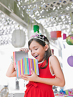 Young girl (7-9) opening birthday present at party