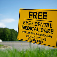 A placard advertises the Remote Area Medical clinic in Wise, Virginia July 20, 2012.  Organizers hope to bring free medical, dental and vision care to more than 3500 uninsured and underinsured people in the rural Virginia area.  REUTERS/Mark Makela   (UNITED STATES)