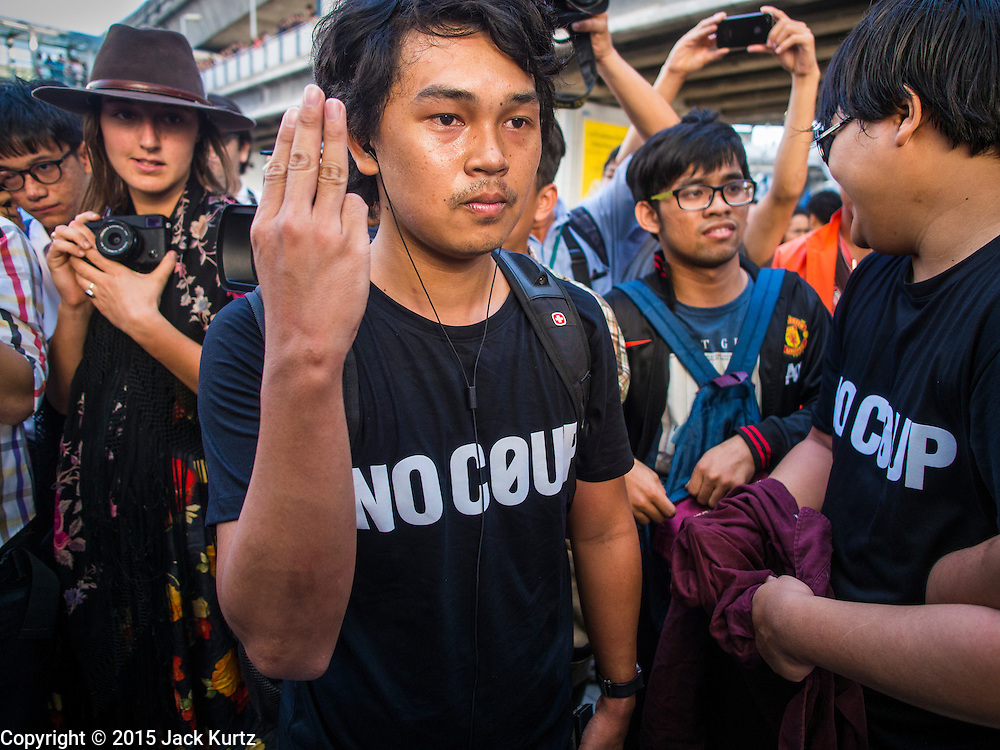 "14 FEBRUARY 2015 - BANGKOK, THAILAND:  An anti-coup protestor holds up the three finger salute from the ""Hunger Games"" movies during an anti-coup protest in Bangkok. The salute is used by protestors to show opposition to the military government. Showing the salute is grounds for arrest under Thailand's martial law. Dozens of people gathered in front of the Bangkok Art and Culture Centre in Bangkok Saturday to hand out red roses and copies of George Orwell's ""1984."" Protestors said they didn't support either Red Shirts or Yellow Shirts but wanted a return of democracy in Thailand. The protest was the largest protest since June 2014, against the military government of General Prayuth Chan-Ocha, who staged the coup against the elected government. Police made several arrests Saturday afternoon but the protest was not violent.     PHOTO BY JACK KURTZ"