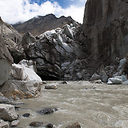 """The mighty Bhagirathi (Ganges) River emerges with force from the toe of the Gangotri Glacier at Gaumukjh - literally, """"Cow's Mouth""""; Uttarakhand, India."""