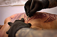 Venezuelan Body Modification artist Emilio Gonzalez doing a Scarification at aTattoo and piercing convention in Mons, Belgium on March 20, 2005.