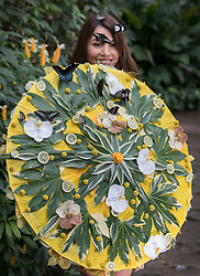 © Licensed to London News Pictures. 12/01/2018. Wisley, UK. Jessie Baker holds a floral parasol to attract butterflies during a photocall for Butterflies in the Glasshouse at RHS Garden Wisley. Running from from 13 January - 4 March 2018 - over 50 species are let loose in the glasshouse to fly freely among the Tropical Zone to allow interaction with visitors.Photo credit: Peter Macdiarmid/LNP