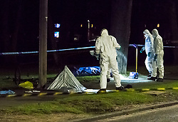 © Licensed to London News Pictures. 14/12/2017. South Ockendon, UK. A body lies covered in the street as police forensics examine personal belonging, including a bike and shoes, at the scene of a murder in the Dilkes Park area of Such Ockendon in Essex. A young man died after being assaulted by two men who then made off in a car. Photo Credit Simon Ford/LNP