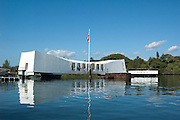 The Arizona Memorial reflects in the waters of Pearl Harbor in Hawaii.
