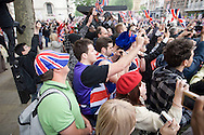 A crowd of onlookers in Whitehall, London, cheering as the newly-wed Prince William and Catherine Middleton drive from the marriage ceremony towards Buckingham palace. The wedding was held at Westminster Abbey. Tens of thousands of people lined the streets to wish the couple well before and after the ceremony.