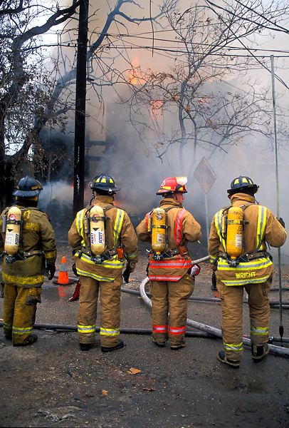 Stock photo of a group of firemen with oxygen tanks work street side at a fire.
