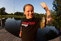 YOUNG FEMALE ANGLER WITH A NEWLY CAUGHT BLUEGILL