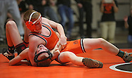 Prairie's Dylan Kleinschmidt works on pinning Linn-Mar's Kyle Tupper during the 113-pound bout of the dual between Linn-Mar and Cedar Rapids Prairie at Prairie High School in Cedar Rapids on December 12, 2013.