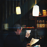 A middle aged man reading a newspaper in a coffee shop