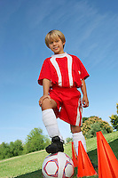 Boy (7-9 years) soccer player holding foot on ball, portrait
