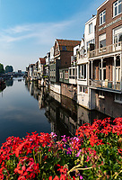 Homes along the canal in Gorichem, Netherlands are attached to each other, rise up to three stories and built on pilings into the water. Bright flowers decorate the bridge over the canal.
