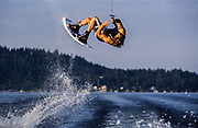 A wakeboarder flipping behind a speed boat.