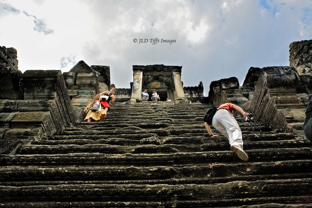 One tourist climbs and another descends the very steep stairway up to one of the towers on top of Angkor Wat.  A couple at the very top looks down.