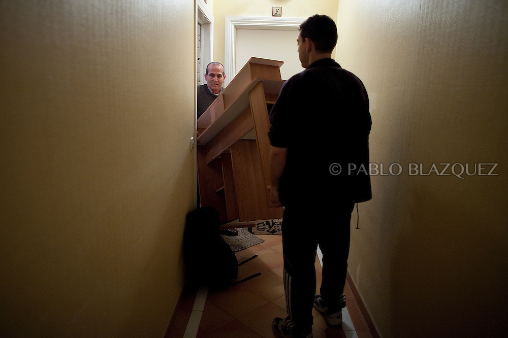 Anuar Jalil (L) carries furniture out of his home in the late hours on February 28 2012. Bulgarian Tatyana Roeva, and husband Anuar Jalil 55, from Libano, await their second evition since last June 2011 their first eviction meant the starting of the Anti-eviction movement. A day before their eviction February 29, 2012 a demonstration of hundreds of people takes part in Madrid claiming a lieu of payment for evicted families and social accomodation. During the demonstration lawyer Rafael Mayoral and the Anti-eviction organization got a deal with BBVA Bank for a lieu of payment of 269.000, plus two months paid accomodation, but the couple needs to leave their house that night.