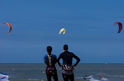 Kitesurfers watch fellow surfers fly through the air over the waters of the North Sea. (Photo © Jock Fistick)