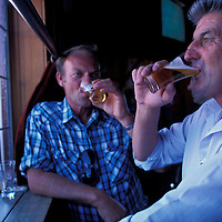 Australia, Tasmania, (MR) Max Long & Darryl Pritchard down beers at Clarendon Arms Hotel pub in downtown Evandale.